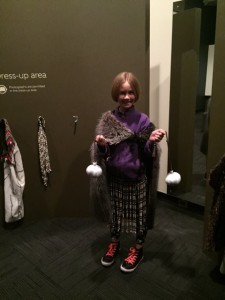 Zoe dressing up in the  maori  cloakes and baskets area of the museum.